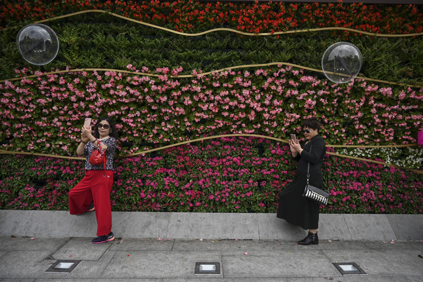 Women take selfies next to the promenade along the Bund in Shanghai, Oct. 14, 2019. Hector Retamal/AFP/VCG