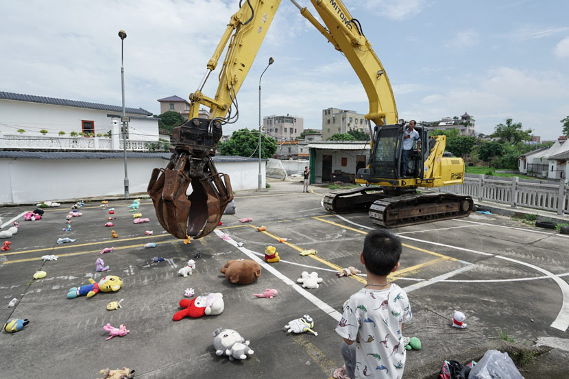 An excavator picks up a doll as part of a performance art piece by Chinese artist Nut Brother in Shenzhen, Guangdong province, August 2019. The work criticized the renewal plan's impact on Baishizhou residents. From @坚果兄弟 on Weibo