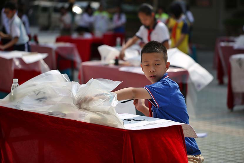 The wind whips up plastic table linings during a primary school calligraphy competition in Guangzhou, Guangdong province, Oct. 24, 2019. VCG