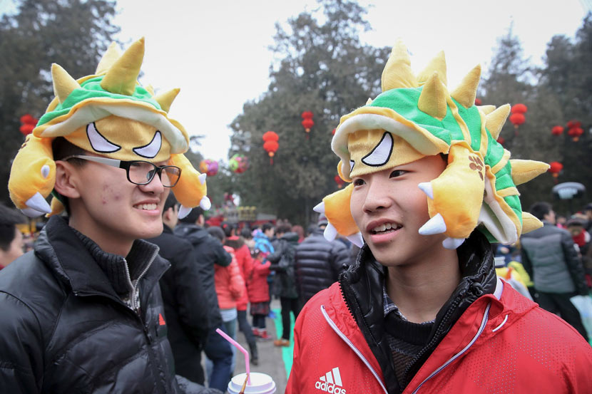 "Two young men wear hats styled as Armordillo, a character from the game ""League of Legends,"" during a temple fair in Beijing, Feb. 1, 2014. Chen Xiaogen/VCG"