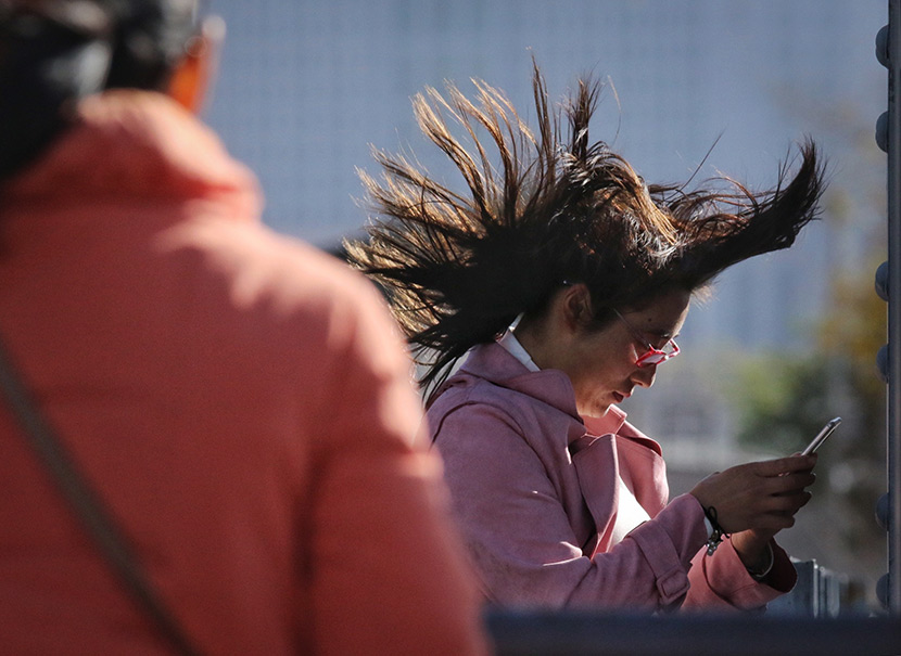 Wind blows through a woman's hair in Harbin, Heilongjiang province, Oct. 31, 2019. Zhang Shu/IC