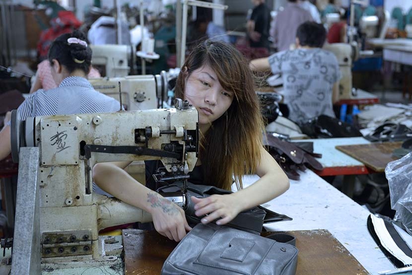 Zheng Ting works in a garment processing factory workshop in Dongguan, Guangdong province, June 8, 2012. Zhan Youbin for Sixth Tone.
