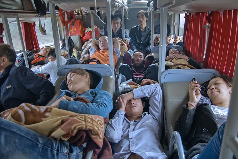 A group of migrant workers head home on a bus from southern Shenzhen to central Hubei via Dongguan, Guangdong province, Oct. 30, 2011. Zhan Youbin for Sixth Tone.