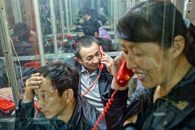 Migrant workers call their families in Dongguan, Guangdong province, Jan. 1, 2012. Since many migrant workers didn't have a mobile phone, they'd usually go to the telephone booth for relatively cheaper long-distance calls. Zhan Youbin for Sixth Tone.
