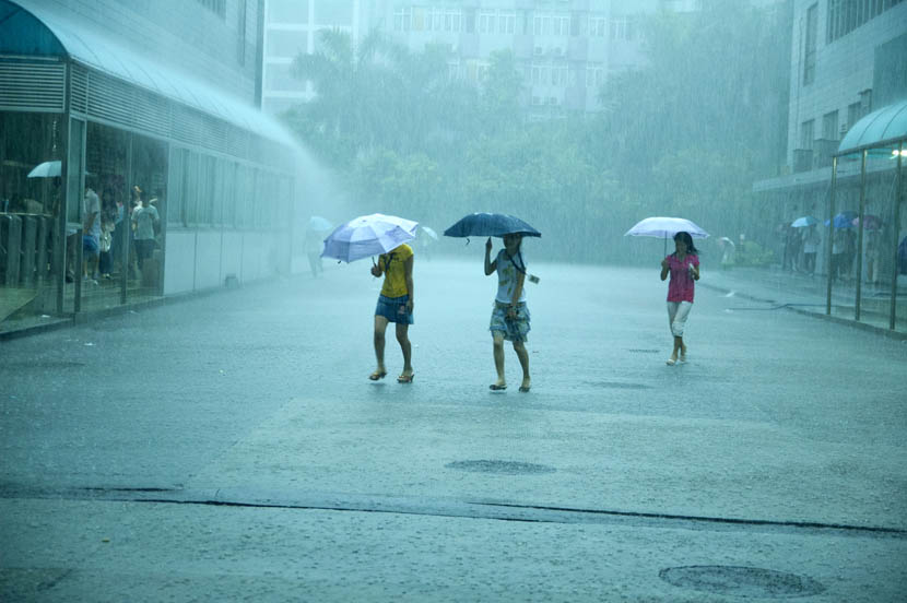 Workers in heavy rain on their way to work in Dongguan, Guangdong province, June 13, 2008. Zhan Youbin for Sixth Tone.