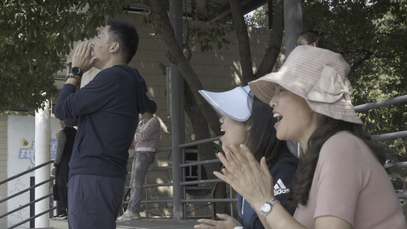 Parents of young players cheer during a soccer match in Shanghai, October 2019. Sixth Tone