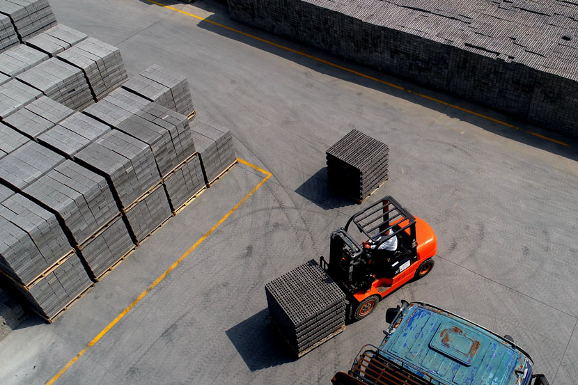 A forklift transfers bricks made from construction waste at a renewable resources company in Nantong, Jiangsu province, March 29, 2019. Qiu Wenshan/VCG