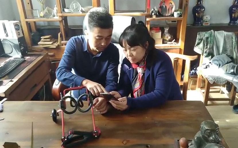 Gao Xiaodong (left) and his wife Fu Lijuan look at a client's dog on their phone in Huludao, Liaoning province, 2019. Courtesy of Gao Xiaodong