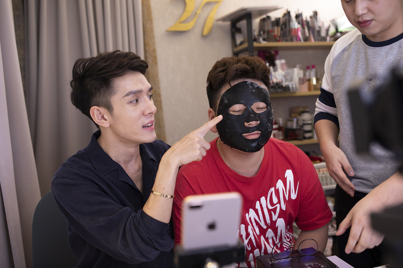 Li Jiaqi (in black) and his assistant promote a face mask during a livestream in Shanghai, Oct. 26, 2018. Ning Jing/VCG