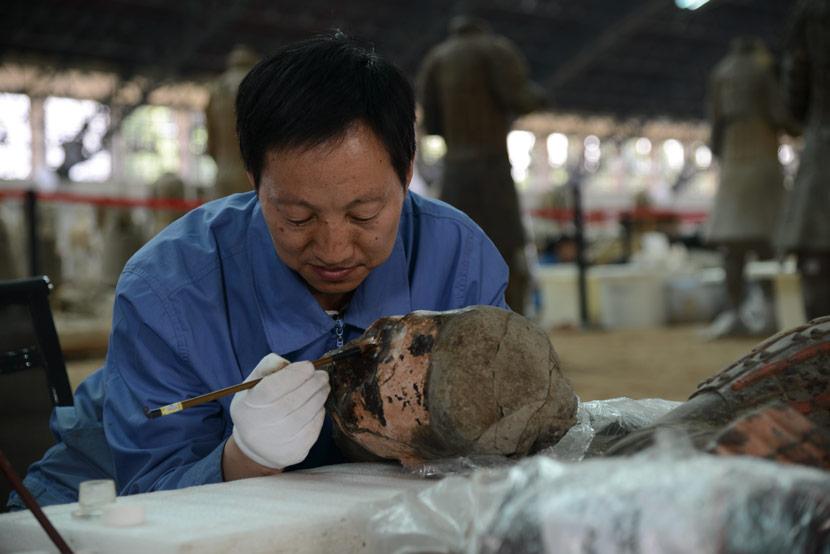 Restorer Lan Desheng fixes the head of a terra-cotta warrior at the Emperor Qin Shi Huang Mausoleum Museum in Xi'an, Shaanxi province, 2013. Courtesy of Lan Desheng