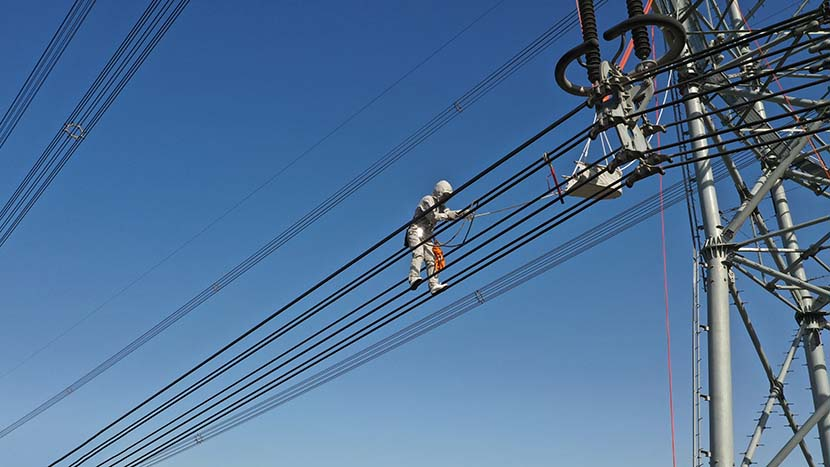 Electrical worker Liu Hongji does the first live work on a 1000kV AC ultra-high voltage (UHV) transmission line in Cangzhou, Hebei province, Nov. 19, 2019. Hu Xiaolong/VCG