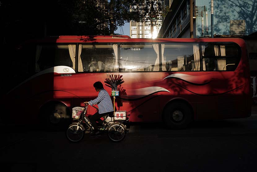 An ice-sugar gourd vendor passes a bus in Guangzhou, Guangdong province, Nov. 21, 2019. VCG