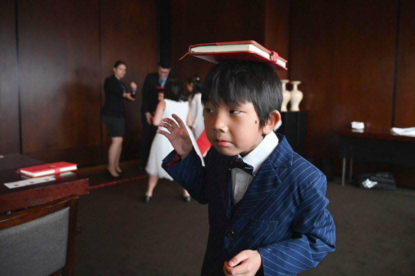 A boy practices balancing a book on his head during an etiquette and manners class in central Shanghai, June 1, 2019. Etiquette classes can cost almost $100 an hour. Hector Retamal/AFP/VCG