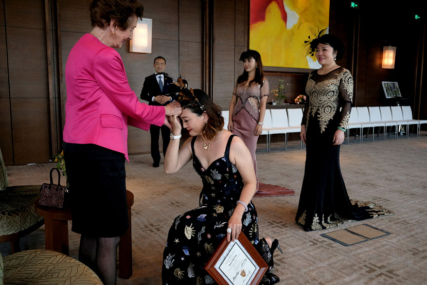 A participant takes a knee before former Australian model June Dally-Watkins after receiving an etiquette certificate in Guangzhou, Guangdong province, Oct. 8, 2017. Bobby Yip/Reuters/VCG