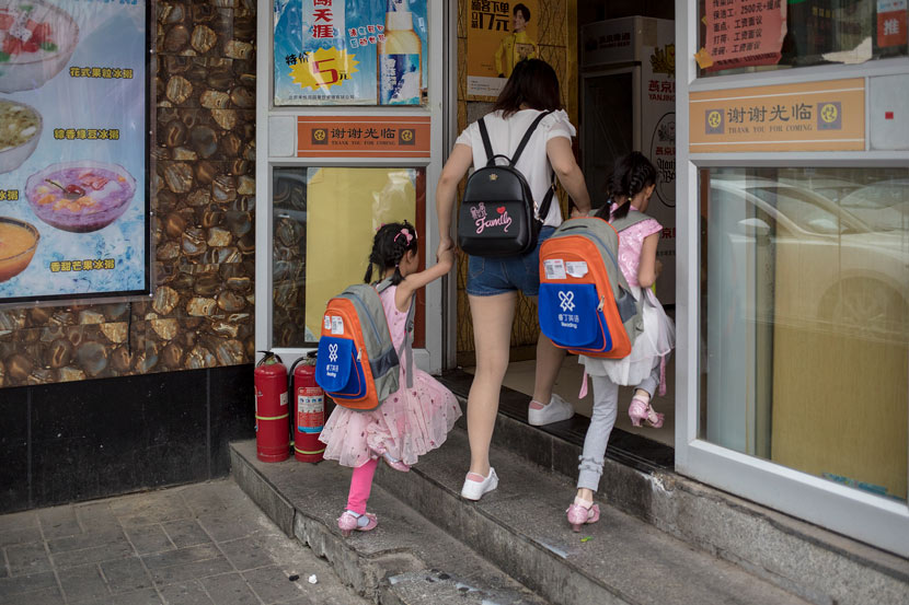 A mother takes her children to lunch after an English training class in Beijing, May 26, 2018. Li Jianguo/VCG