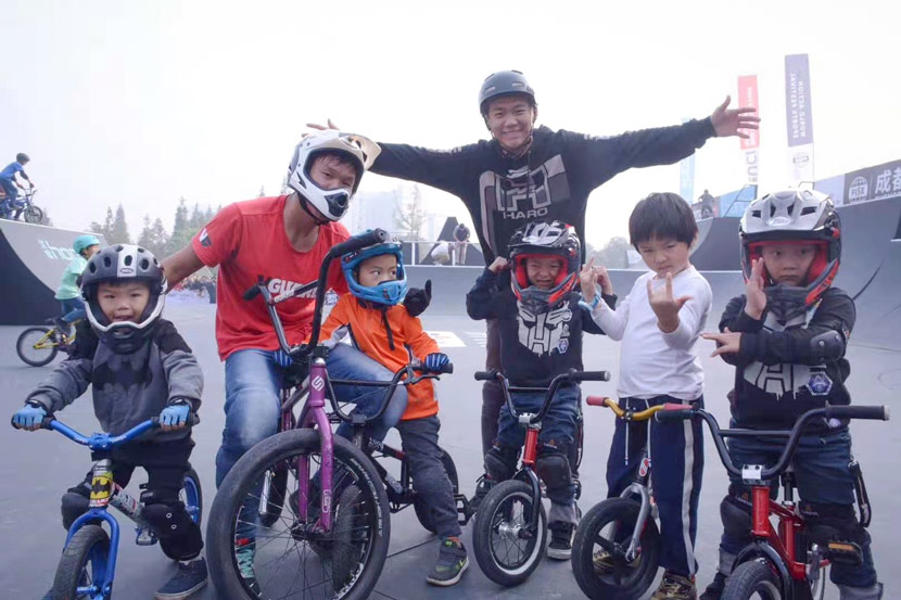 Bao Jiafu (in red) and his friend pose for a photo with young BMX riders in Chengdu, Sichuan province, November 2017. Courtesy of Bao Jiafu