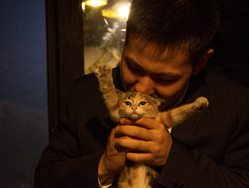 A rider plays with a feline friend at the Cat Crew BMX bike shop in Shanghai, Nov. 12, 2019. Jiang Feng for Sixth Tone