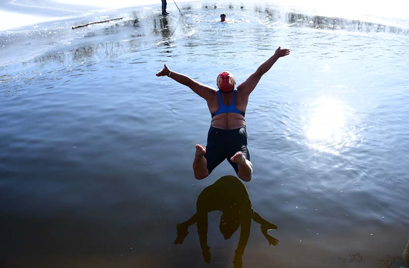 A woman jumps into a partially frozen lake at a park in Shenyang, Liaoning province, Dec. 2, 2019. Zhang Hong/IC