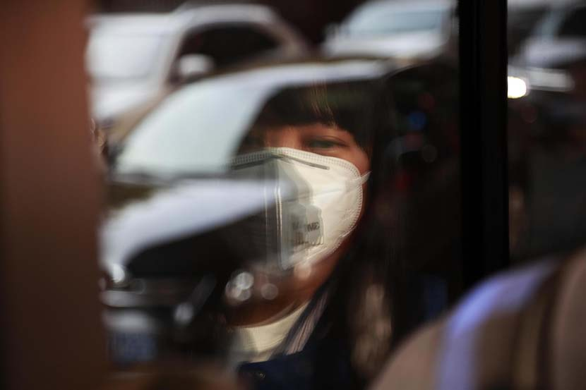 A woman on a bus wears a mask on a day of heavy smog in Shanghai, Dec. 4, 2019. Tang Yanjun/CNS/VCG