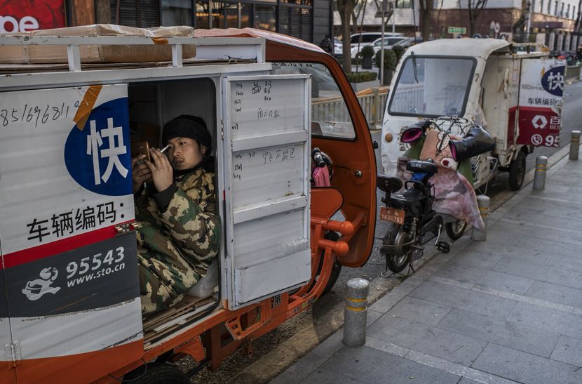 A courier driver watches a video on his cell phone while taking a break in a shopping district in Beijing, Dec. 10, 2019.