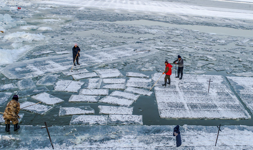 Workers cut ice at an ice mining site in Harbin, Heilongjiang province, Dec. 11, 2019.