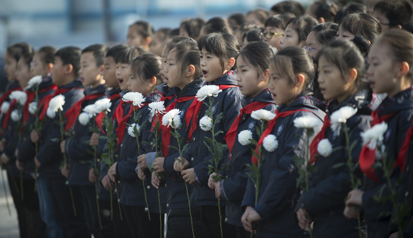 Children attend a remembrance event for the victims of the 1937 Nanjing Massacre at one of the mass burial sites in Nanjing, Jiangsu province, Dec. 13, 2019. Li Yuze/Xinhua