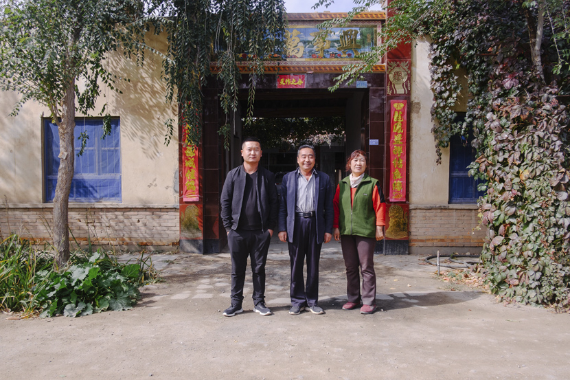 Liu Hongyou (center) poses for a photo with his family members in front of their house in Minqin County, Gansu province, Oct.14, 2019. Wu Huiyuan/Sixth Tone