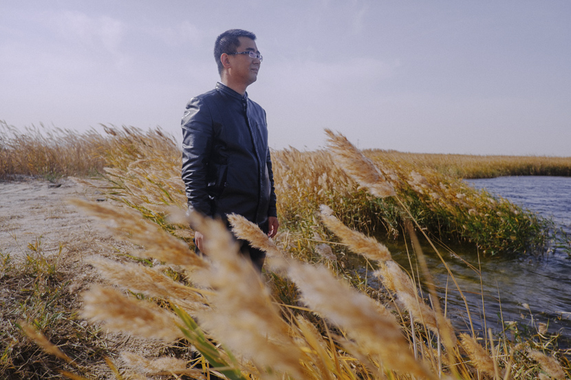 A senior official at Minqin's water conservancy bureau poses for a photo near Qingtu Lake in Gansu province, Oct. 19, 2019. Wu Huiyuan/Sixth Tone