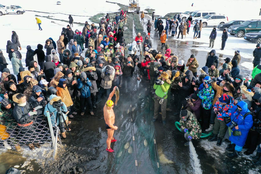 People gather to watch fishers haul in their catch on the partially frozen Nuogan Lake in the Hulun Buir Grasslands of Inner Mongolia, Dec. 18, 2019. Liu Lei/Xinhua