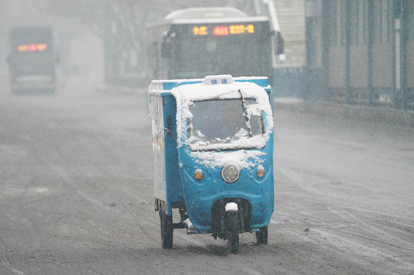 Snow obscures the windshield of a courier's motorized tricycle in Beijing, Dec. 16, 2019. Qu Zonghuan/Xinhua