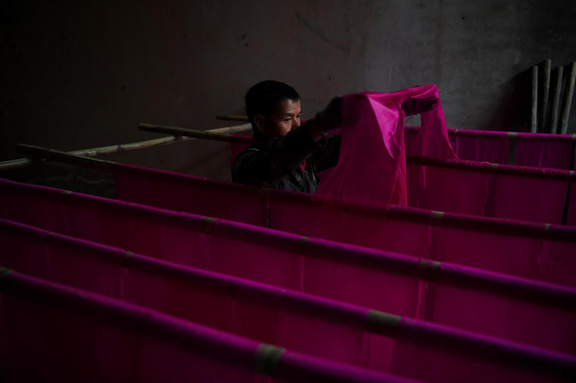 A craftsman dries thin sheets of cotton before rolling them into 1.2-meter sticks of joss paper, which are commonly burned as offerings, in Tonghai County, Yunnan province, Nov. 28, 2019. Kang Ping/CNS/VCG