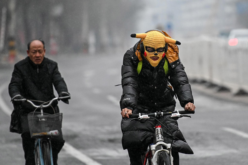 A cyclist wears a Pikachu face mask to keep warm on a snowy day in Taiyuan, Shanxi province, Nov. 29, 2019. Wei Liang/CNS/VCG