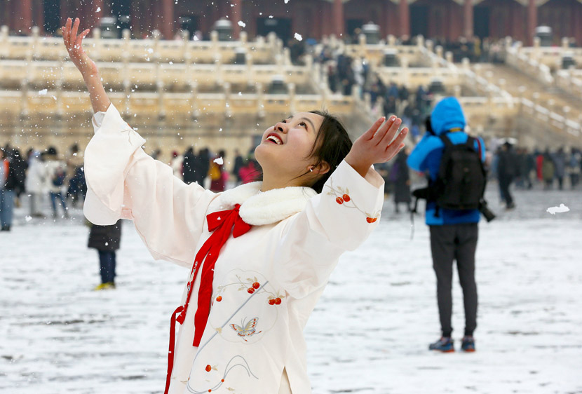 A woman throws snow into the air while posing for photos at the Palace Museum in Beijing, Nov. 30, 2019. VCG