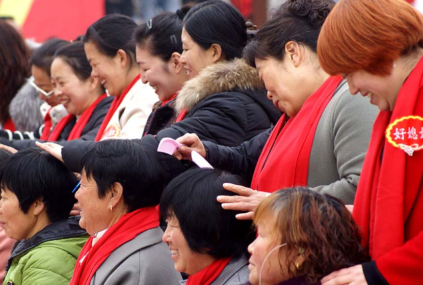 Women who received public awards for good behavior groom their mothers-in-law in Jiyuan, Henan province, March 8, 2018. Tuchong