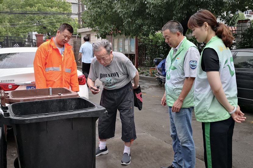 Volunteers explain waste sorting to an elderly resident in Shanghai, June 27, 2019. IC