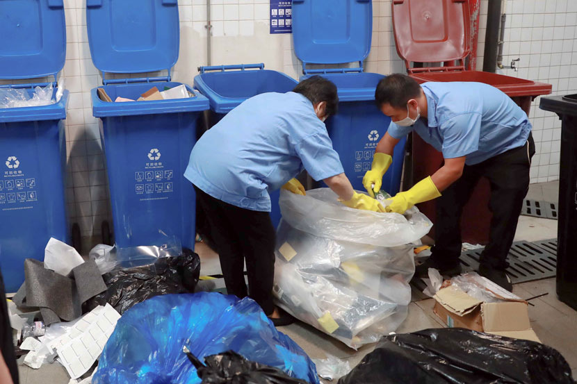 Workers sort waste in front of trash bins in Shanghai, July 1, 2019. Tuchong