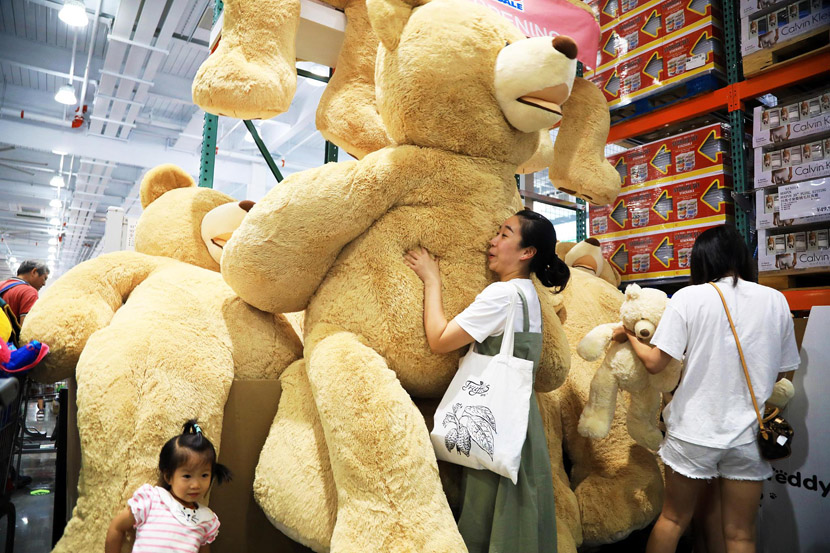 A woman holds a teddy bear at Costco's first outlet store in the Chinese mainland in Shanghai, Aug. 29, 2019. Tang Yanjun/CNC/VCG