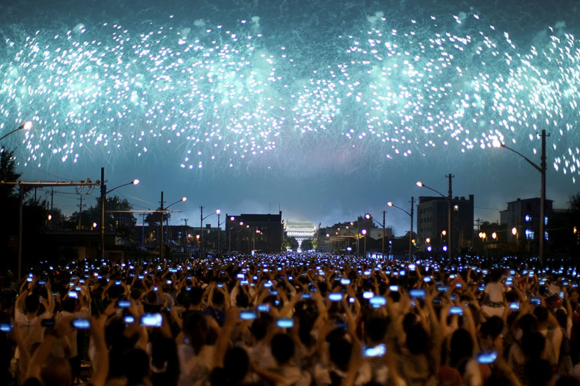 People raise their phones to the sky to record a Beijing fireworks show celebrating the 70th anniversary of the founding of the People's Republic of China, Oct. 1, 2019. Aly Song/Reuters/VCG