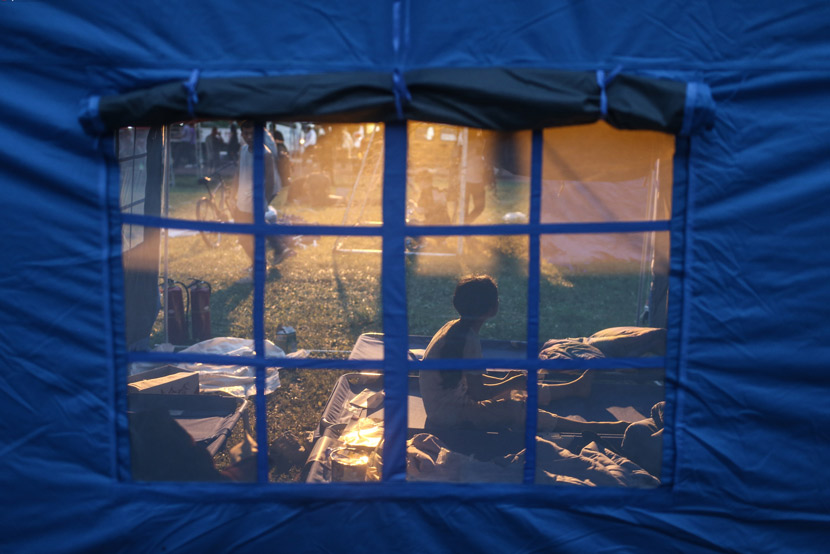 A child looks into the distance from inside a tent at a temporary camp set up for earthquake survivors in Changning County, Sichuan province, June 18, 2019. Peng Ziyang/Beijing News/IC