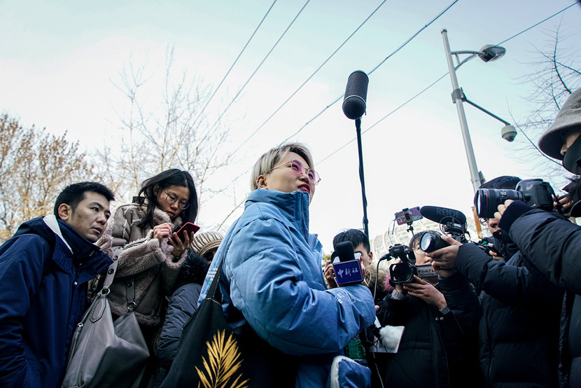 Xu Zaozao (center), the plaintiff of a case on the right to freeze eggs as a single woman, does an interview in front of the court after the first hearing in Chaoyang District in Beijing, Dec. 23, 2019. Cai Xingzhuo/JIEMIAN