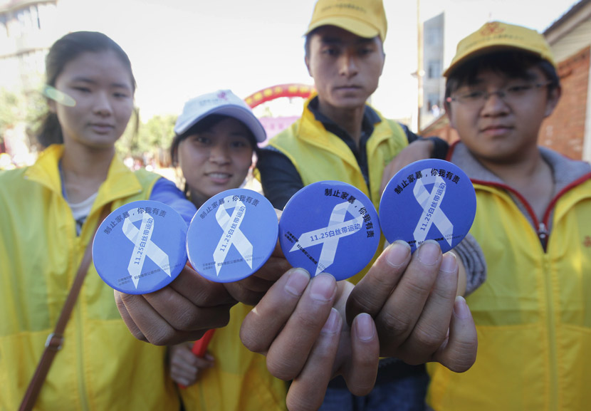 Volunteers pose for a photo with White Ribbon badges during an activity on anti-domestic violence in Kunming, Yunnan province, Nov. 25, 2019. Tuchong
