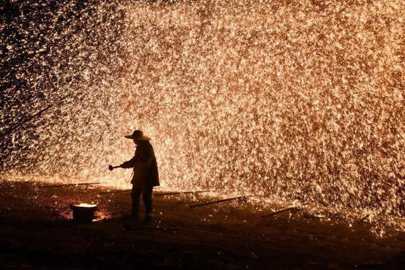 "A man performs ""datiehua,"" or ""strikingironflowers,"" as part of the New Year celebrations in Zhangjiakou, Hebei province, Jan. 1, 2020. Zhang Zifa/CNS"