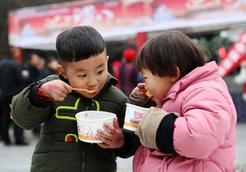 Two children enjoy porridge in honor of the Laba Festival, held on the eighth day of the last month of the lunar year, in Chongqing, Jan. 2, 2020. Yang Min/Xinhua