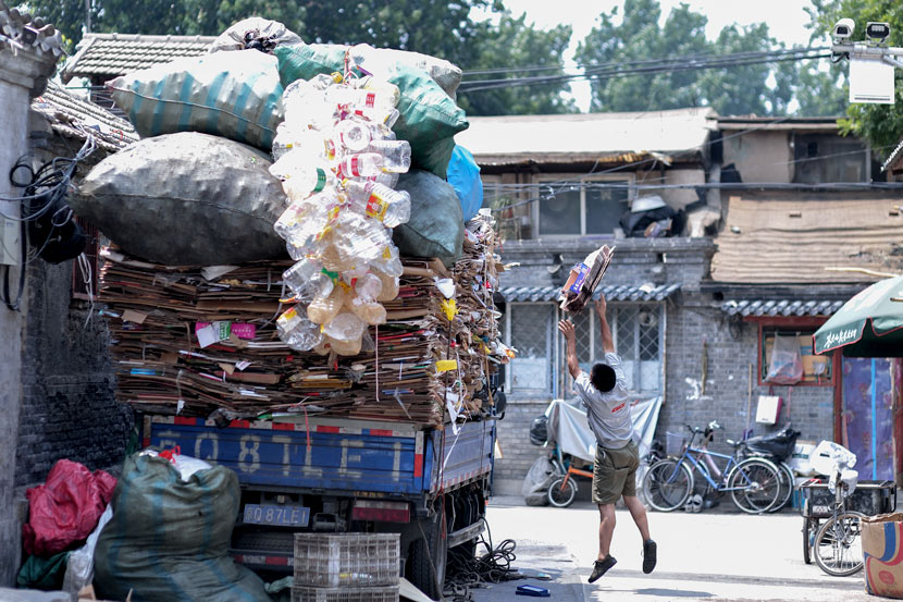 A recycler throws cardboard onto his truck in Beijing, June 10, 2018. Tuchong