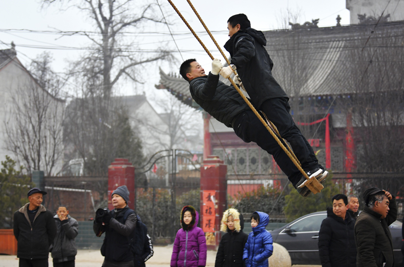 Villagers play on a swing, a traditional local custom celebrating the upcoming Spring Festival, in Zhouzhi County, Xi'an, Shaanxi province, Jan. 9, 2020. Liu Xiao/Xinhua