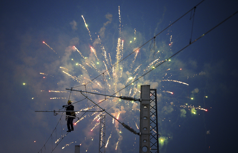 A worker sets up electric cables during a display of fireworks in Xi'an, Shaanxi province, Jan. 7, 2020. Liu Xiao/Xinhua