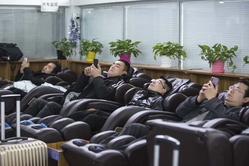 Passengers use shared massage chairs at a railway station during the first day of the Spring Festival travel rush in Hangzhou, Zhejiang province, Jan. 10, 2020. Chen Zhongqiu for Sixth Tone