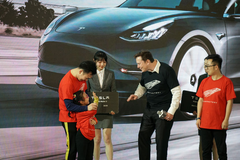 Tesla CEO Elon Musk (center) greets customers during a delivery ceremony for the company's China-made Model 3 sedans in Shanghai, Jan. 7, 2020. Bao Yumeng for Sixth Tone