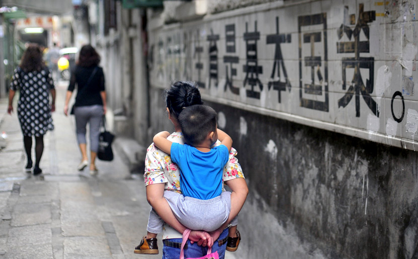 A woman holding a child walks past a slogan for family planning in Guangzhou, Guangdong province, Nov. 6, 2015. Tuchong