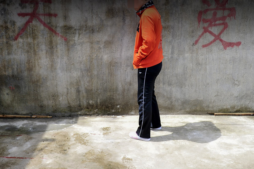 A teenager with autism stands alone in Zhangjiajie, Hunan province, March 29, 2014. Tuchong